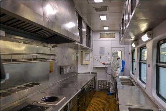 防疫员胡亚东在餐车厨房内喷洒消毒水。新华社记者 张楠 摄