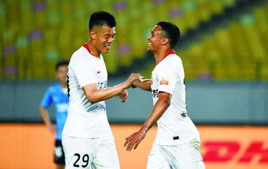 22日,长春亚泰队球员埃里克(右)与队友谭龙在比赛中庆祝进球。(新华社发)