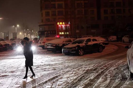 1月3日晚,河南许昌襄城县,风雪中裹着大衣出行的路人。