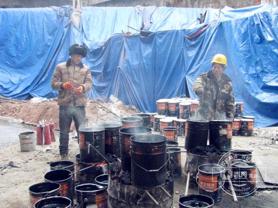 工人正在熬制防水涂料