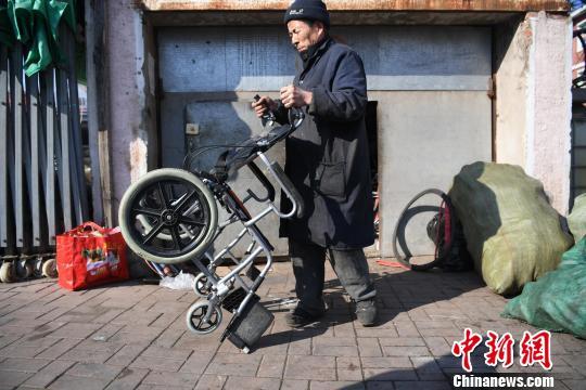 马希国在修车铺前修车 张瑶 摄