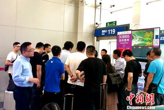 图为大批乘客向成都双流机场工作人员了解延误原因。 黄心玥 摄