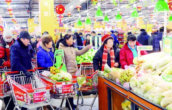 22日,长春市民在超市购买蔬菜。新春佳节即将来临,长春市节日商品货足价稳。 贾春文 摄