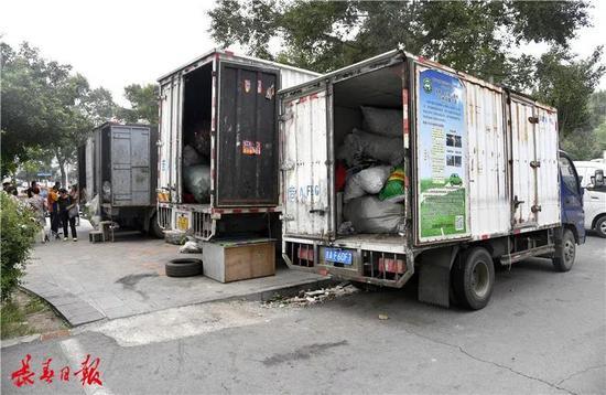 收购好的物品直接装车,几辆分别装载不同物品的货车并排停放,秩序井然,现场环境良好