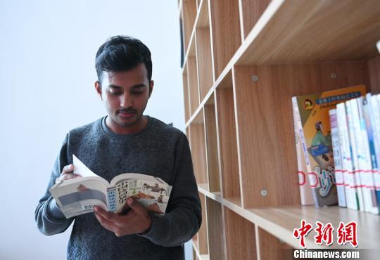 罗欧汉在学校的阅读室翻阅诗集。 张瑶 摄