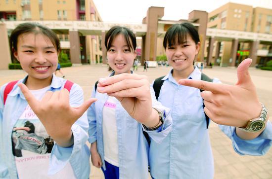 """7日,在河北省邯郸市第一中学考点,三名考生摆出""""678""""手势,寓意""""录取吧""""。 (新华社发)"""