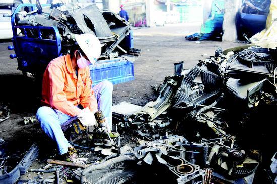 近日,广州市金属回收有限公司购销部工人精细拆解报废汽车零部件。 (新华社发)