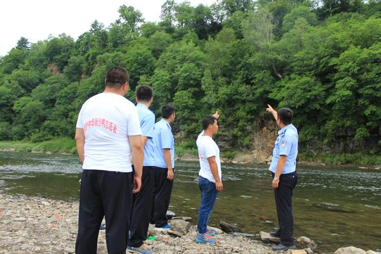 保护中华秋沙鸭志愿者位巡护民警介绍鸭巢分布情况及重点活动水域