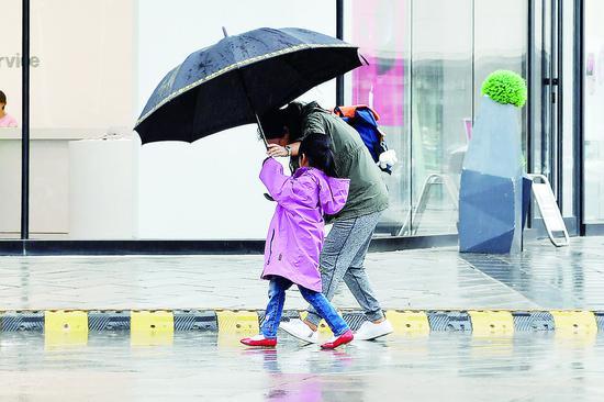 降雨、降温让市民重新穿上厚外套。 张扬 摄