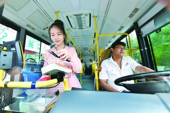 乘客在152路公交车上使用手机支付。 张扬 摄