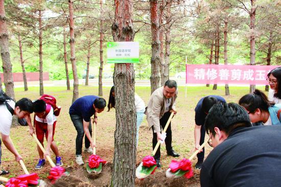 """吉大外国语学院的毕业生在中心校区毕业生纪念林认领""""根系吉大""""2018届毕业生纪念树。 于恒 摄"""