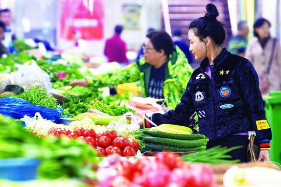 16日,市民在江苏南京一家农贸市场购买蔬菜。当日,国家统计局发布数据,9月份全国居民消费价格指数(CPI)同比上涨2.5%。 (新华社发)