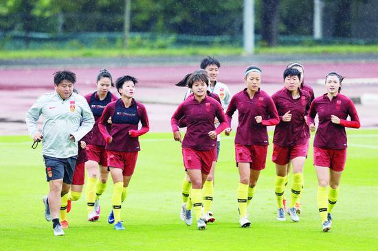 19日,中国女足球员在训练前热身。 (新华社发)
