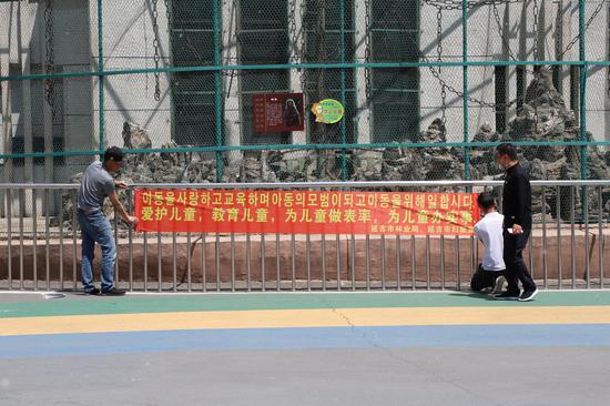 公园工作人员正在悬挂宣传条幅。石拓野 摄