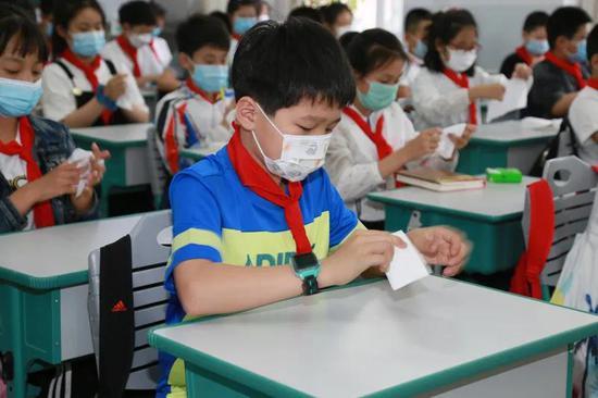 吉林市一实验学生在教室内进行手部消毒。