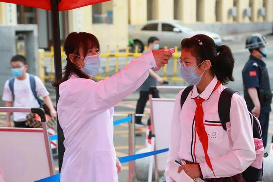 吉林市第一实验小学的老师在给孩子测温。
