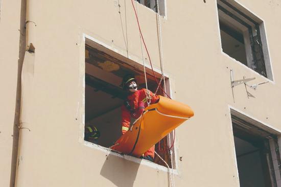 """演练中,消防人员将""""伤者""""转运至楼下。"""