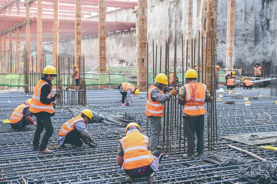 在轨道交通6号线施工现场,工人进行钢筋绑扎作业。张扬 摄