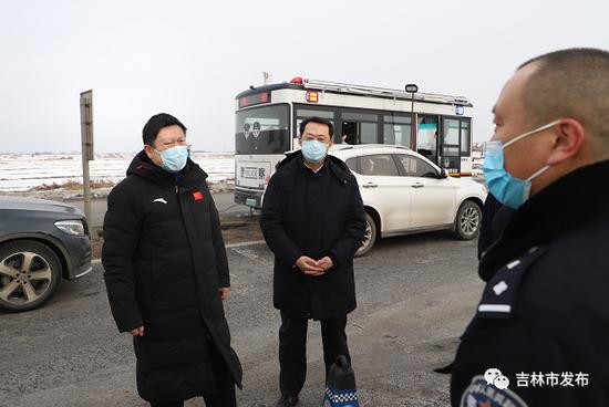 吉林市委书记贺志亮(左)在舒兰平安镇新发高速疫情防控执勤点了解疫情防控措施落实情况,并对工作人员致以节日问候。