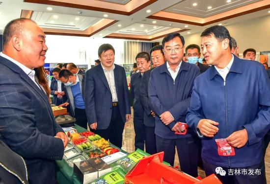 吉林市委书记王庭凯(右一)、市长贺志亮(左二)在吉白两市扶贫产业协作对接洽谈会上,观看了解扶贫对接企业的产品。