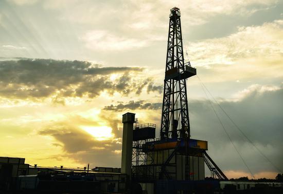 """夕阳下的""""地壳一号""""万米钻机整机系统(6月1日摄)。 新华社记者 许畅 摄"""
