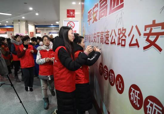 共青团吉林省委志愿者在背景墙上签名