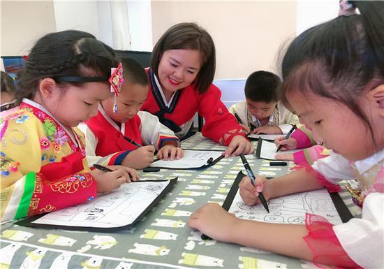 新蕾教师指导幼儿用手中的画笔,描绘美丽家乡
