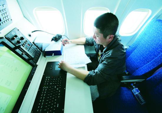 工作人员在MA60增雨飞机上记录数据。