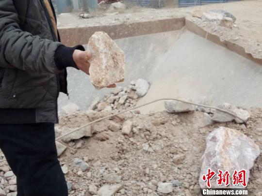 """一位村民说,""""像这样石子厂放炮崩出的石块砸在我家院子里,吓得我们几天不敢睡觉。"""" 赵晖 摄"""