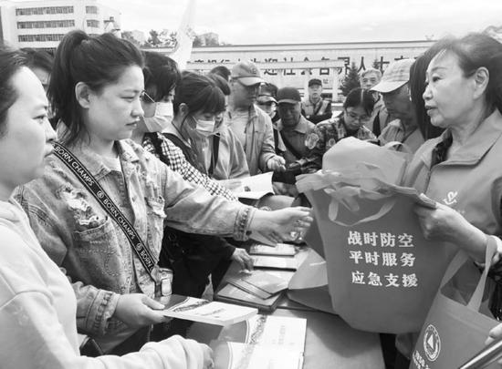 志愿者给行人发放宣传资料。记者左颖摄