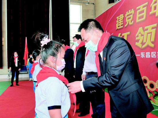 通化市委书记高志国为一年级新入队的学生佩戴红领巾。记者庄新岩摄