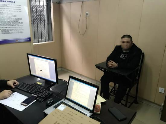 办案民警审讯犯罪嫌疑人。    乐山市公安局供图
