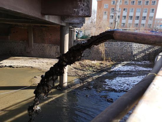 11月18日,龙山实验学校附近的仙人河西侧,竖井里的黑水被水泵抽出后直接排入河中。新京报记者 段睿超 摄
