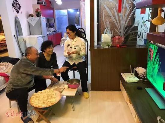 通化观众朱永富与家人一起一边包饺子,一边看央视春晚吉林长春一汽分会场的演出。