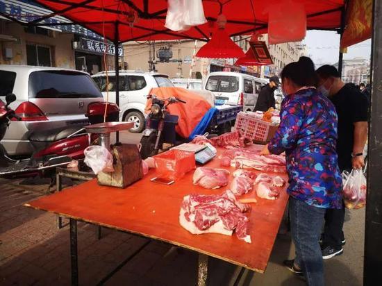 早市上,猪肉摊床前很少有人,摊主很清闲。