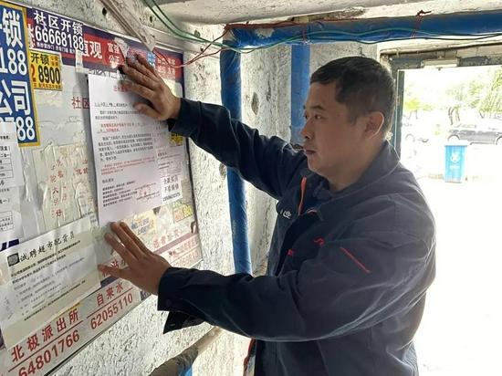 供热人员在单元公示栏张贴注水通知