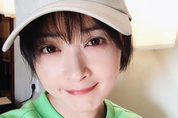 蒋欣短发造型妆容精致 绿卫衣棒球帽出镜一脸甜笑
