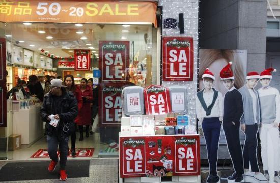 2015年12月19日,在韩国首尔,人们从一家打折的化妆品商店里走出。新华社记者 姚琪琳 摄