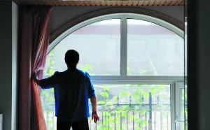 一楼业主拉开窗帘,视线被高墙挡住。