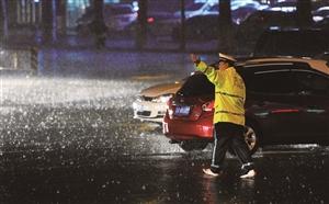 人民大街与自由大路交会处,交警赤着脚在雨中执勤。