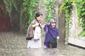 市民在雨中趟水前行。张扬 摄