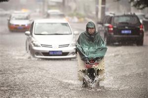 市民在雨中骑行。张扬 摄