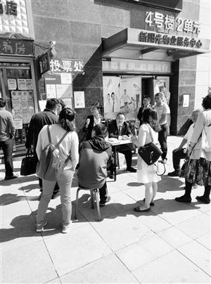 国信物业公司工作人员接受小区居民投票。 刘连宇 摄