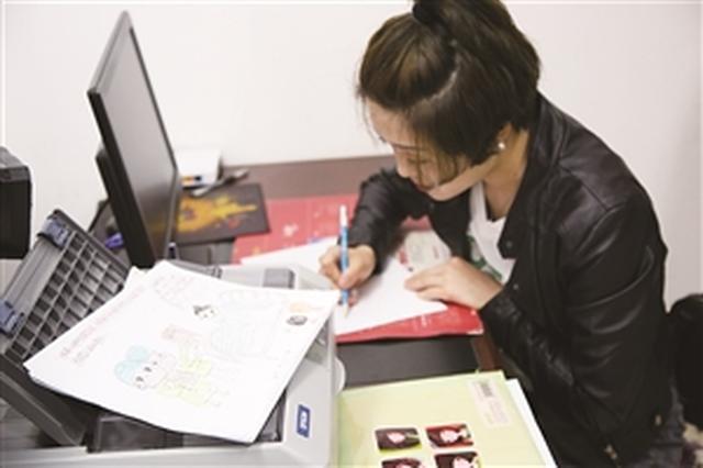 刘峻伊利用业余时间将日常工作绘制成漫画。于慧 摄