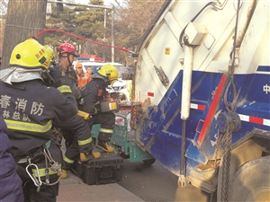 消防官兵破拆垃圾压缩车。