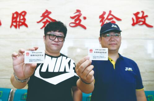 11日,在市公安局朝阳区分局户政大厅,来自香港的李志伟(左)和来自台湾的李豪杰,领取了我省首批港澳台居民居住证。 孙建一 摄