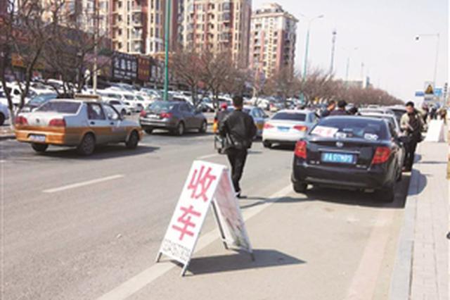 """商贩将""""收车""""字样提示牌摆放到机动车道招揽生意。李子涵 摄"""