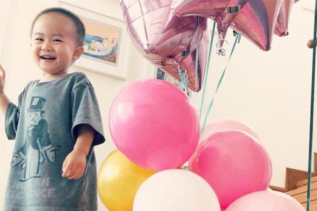 李安琪儿子站在楼梯上摸气球 小脸肉肉笑容很可爱