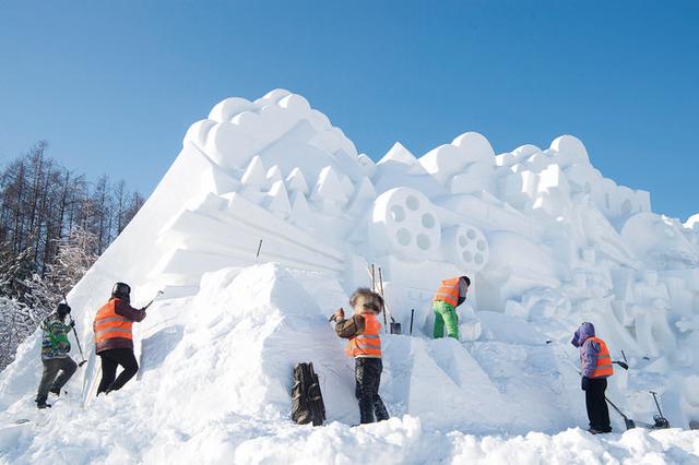 雪雕师在寒冷的冬日里加紧制作大型雪雕《大众冰雪·活力长春》