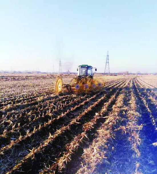 随着保护性工作的推广,各式新型农机登场。图为拖拉机牵引着搂草机在作业,这是保护性耕作的一个环节。